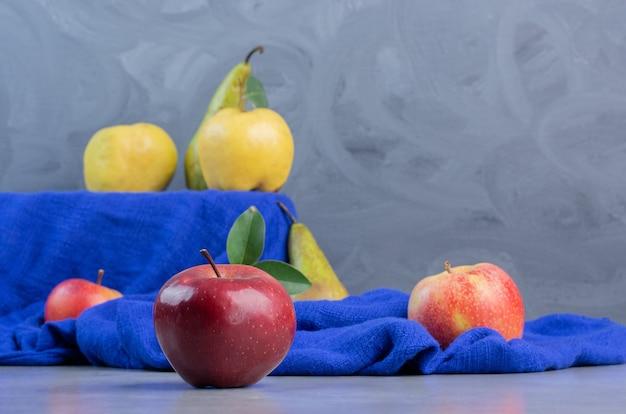 Coings, pommes et poires sur nappe bleue sur fond de marbre.
