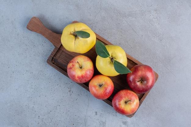 Coings et pommes regroupés sur une planche de bois sur fond de marbre.