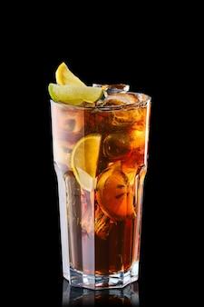 Cola froid avec des tranches de citron vert et citron isolé sur fond noir