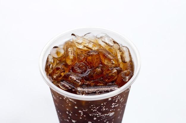 Cola avec de la glace dans une tasse à emporter sur blanc