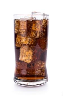 Cola en verre avec des glaçons sur une surface blanche