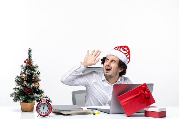 En colère choqué jeune homme d'affaires avec drôle de chapeau de père noël regardant au-dessus dans le bureau sur fond blanc