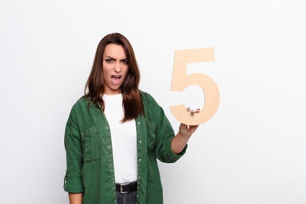 En colère, colère, désaccord, tenant un numéro 5.