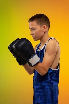 En colère. formation de boxeur professionnel adolescent en action, mouvement isolé sur fond dégradé à la lumière du néon. coup de pied, boxe. concept de sport, mouvement, énergie et mode de vie sain et dynamique.