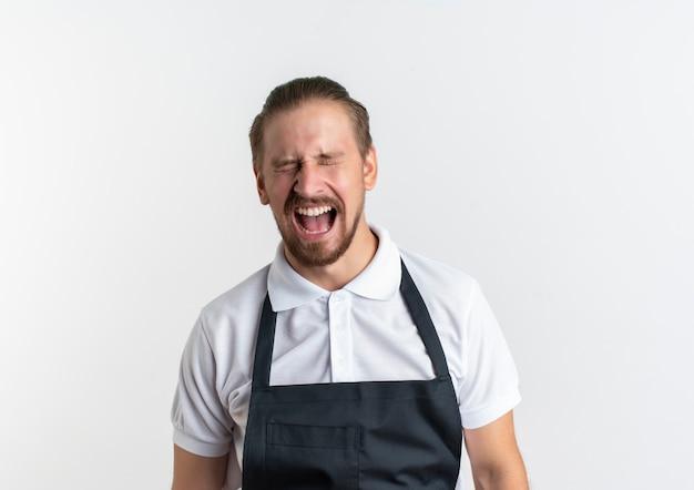 En colère jeune beau coiffeur en uniforme debout avec les yeux fermés et la bouche ouverte isolé sur blanc avec espace copie