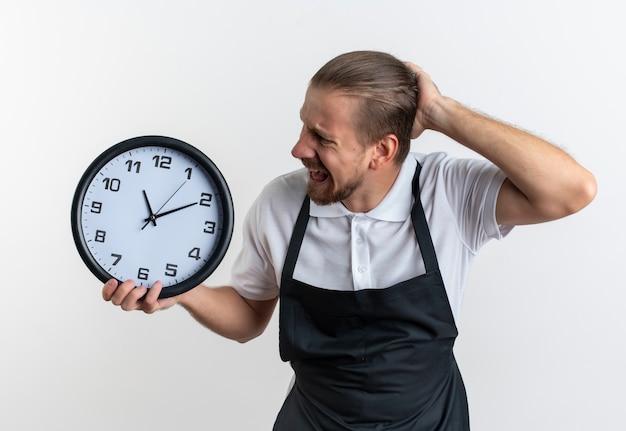En colère jeune beau coiffeur en uniforme tenant et regardant l'horloge avec la main sur la tête isolé sur blanc