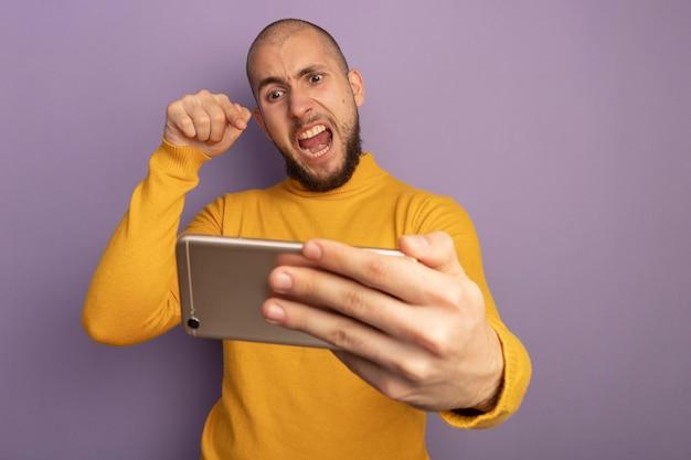 Colère jeune beau mec tenant et points au téléphone isolé sur violet