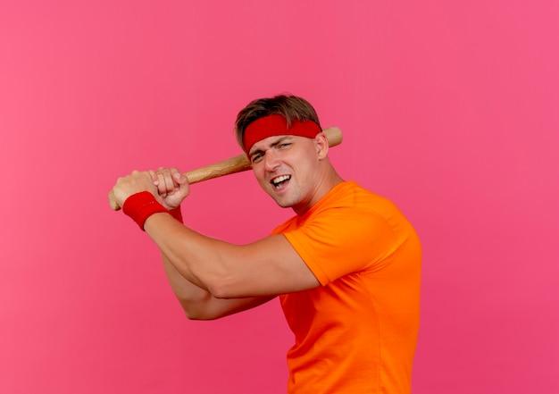 En colère jeune bel homme sportif portant un bandeau et des bracelets tenant une batte de baseball s'apprête à battre isolé sur rose avec copie espace