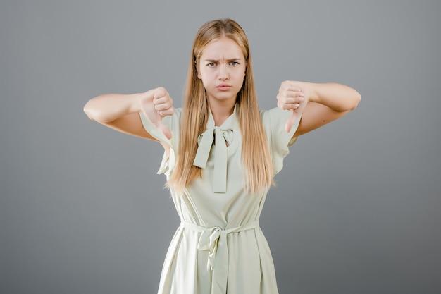 En colère jeune femme blonde montrant les pouces vers le bas isolé sur gris