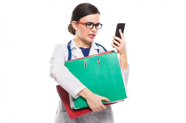 En colère jeune femme médecin avec stéthoscope tenant des cartables et téléphone dans ses mains en uniforme blanc