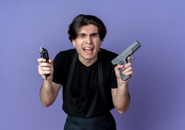 En colère jeune homme beau coiffeur en uniforme tenant une tondeuse à cheveux avec pistolet isolé sur fond bleu