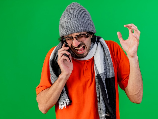 En colère jeune homme malade portant des lunettes chapeau d'hiver et écharpe gardant la main dans l'air parler au téléphone avec les yeux fermés isolé sur mur vert