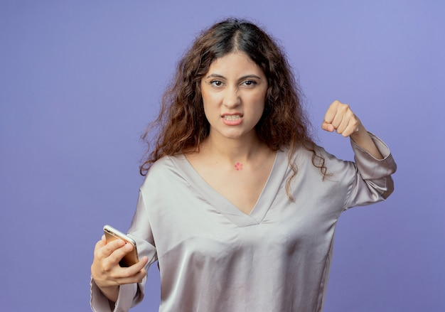 En colère jeune jolie fille tenant le téléphone et levant le poing isolé sur mur bleu
