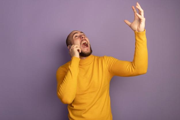 En colère en levant le jeune beau mec parle au téléphone en levant la main isolé sur violet avec copie espace
