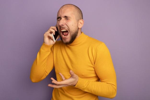 En colère, les yeux fermés, jeune beau mec parle au téléphone isolé sur un mur violet