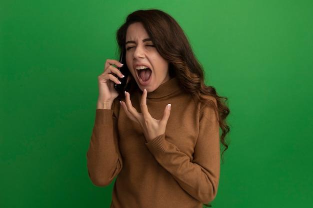 En colère, les yeux fermés, jeune belle fille parle au téléphone isolé sur un mur vert
