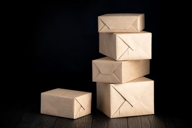 Colis ou cadeaux emballés dans du papier d'emballage sur fond noir