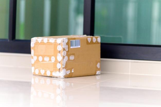 Colis dans une boîte en carton sur le pas de la porte