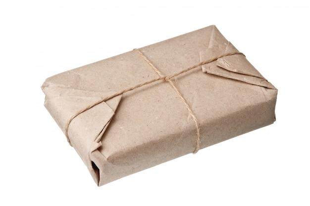 Colis enveloppé de papier kraft brun isolé sur fond blanc
