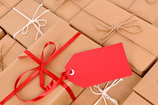 Colis avec étiquette de cadeau rouge