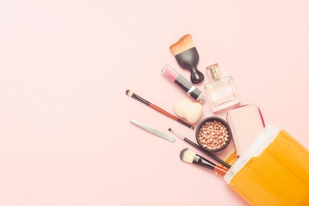 Colis de livraison déballé avec des marchandises sur un fond rose. colis concept, fret, commande en provenance de chine, une variété de produits, boutique en ligne, cosmétiques de soins de la peau et maquillage. mise à plat, vue de dessus.
