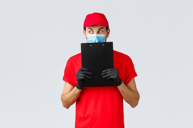 Colis, livraison, quarantaine covid-19, ordres de virement. courrier curieux et excité en uniforme rouge, gants et masque médical pour le visage, détourner le regard intrigant, tenant un presse-papiers avec bon de commande