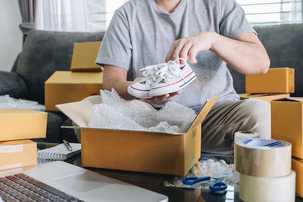 Colis de petite entreprise à expédier au client, jeune entrepreneur pme freelance travaillant avec des chaussures de conditionnement sur le marché en ligne de la livraison de boîtes sur bon de commande et préparant les emballages à la maison