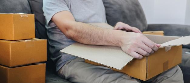 Colis de petite entreprise pour l'expédition, homme heureux ouvrant une boîte de colisage en ligne avec colis assis sur un canapé à la maison.
