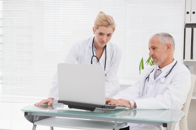 Collaborateur de médecins concentrés utilisant un ordinateur portable
