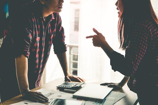 Un collaborateur se dispute avec un ami à propos d'une table de bureau