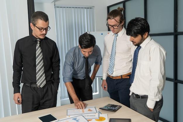 Collaborateurs attentifs analysant soigneusement le rapport financier.