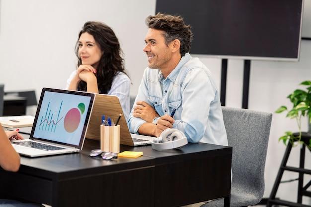 Collaborateurs en coworking avec des ordinateurs