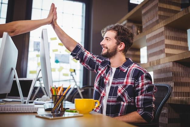 Collaborateurs créatifs high fiving au bureau dans le bureau