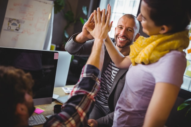 Collaborateurs créatifs high fiving in office
