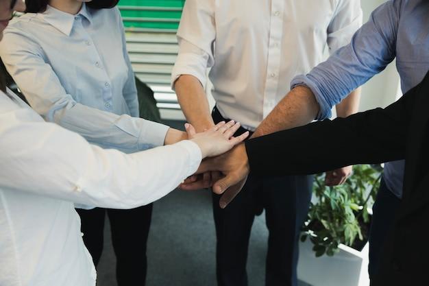 Collaborateurs qui empilent les mains ensemble
