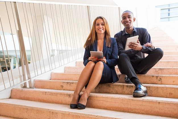 Collaborateurs tenant des tablettes et assis dans les escaliers
