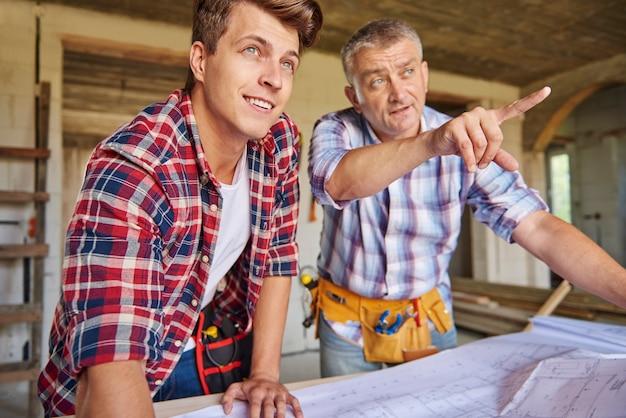 Collaboration de deux charpentiers dans le bâtiment