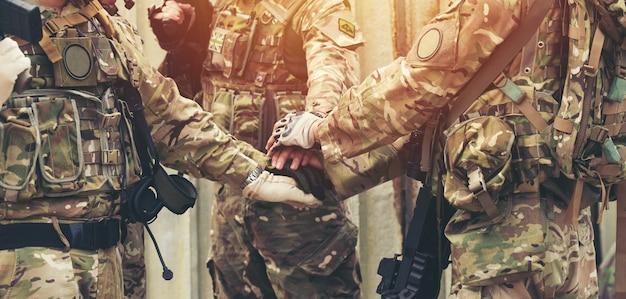 Collaborez ensemble au travail d'équipe des mains au parc en plein air. concept de charité de travail d'équipe, groupe de diverses mains ensemble traitement croisé de personnes soldat militaire en uniforme.