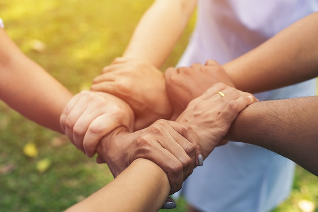 Collaborez ensemble au travail d'équipe des mains au parc en plein air. concept de charité de travail d'équipe, groupe de diverses mains, traitement croisé de personnes dans la nature