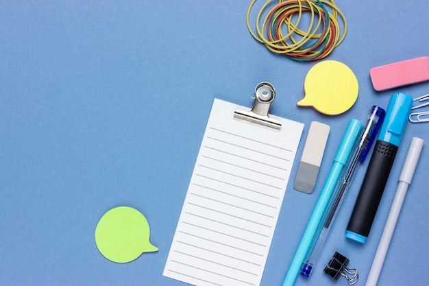 Collage de concept sur un thème financier. planifier un budget ou faire du shopping. liste de contrôle, crayon, papeterie, notes. fond bleu