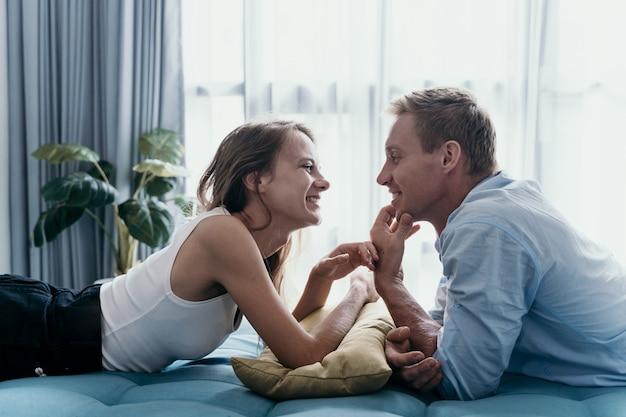 Collage de couple et souriant en position couchée