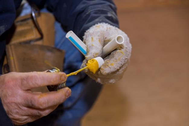 Collage de pièces d'un tuyau d'eau en pvc à l'aide de l'installation d'assemblage de colle de ciment tuyaux en polypropylène de plomberie pour l'eau