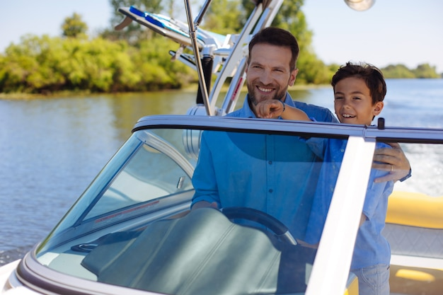 Collage précieux. heureux jeune homme serrant son petit-fils bien-aimé pendant qu'ils naviguent ensemble sur le bateau à moteur