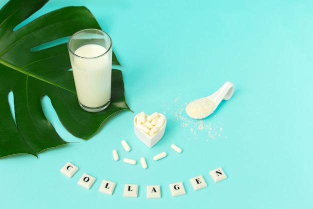 Collagène en poudre, lait et pilules sur fond bleu.