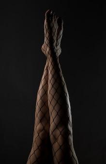 Collants résille noirs sur des jambes fines relevées sur fond de nuit noire