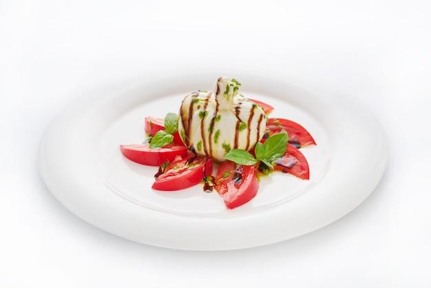 Collation au fromage italien buratta avec tomates et pesto servi sur plaque blanche