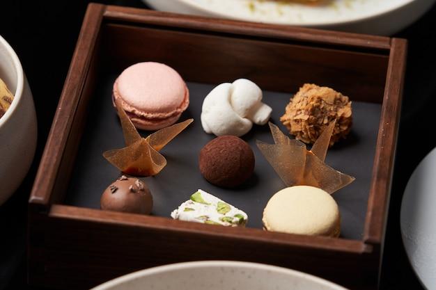 Collation de biscuits sucrés, tranches de gâteau et bonbons au chocolat sur table, gros plan