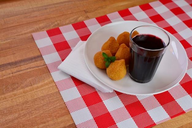 Collation brésilienne de poulet frit, esfihas et pâtisserie au jus de raisin - populaire dans les fêtes locales.