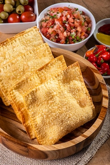Collation brésilienne typique appelée pastel. accompagné de vinaigrette et de poivre sur une table en bois