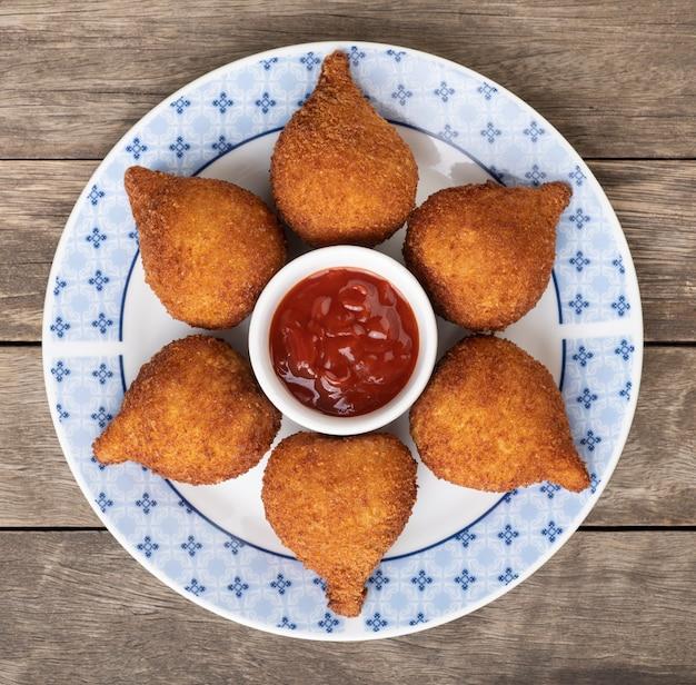 Collation brésilienne typique coxinha sur une assiette avec du ketchup.